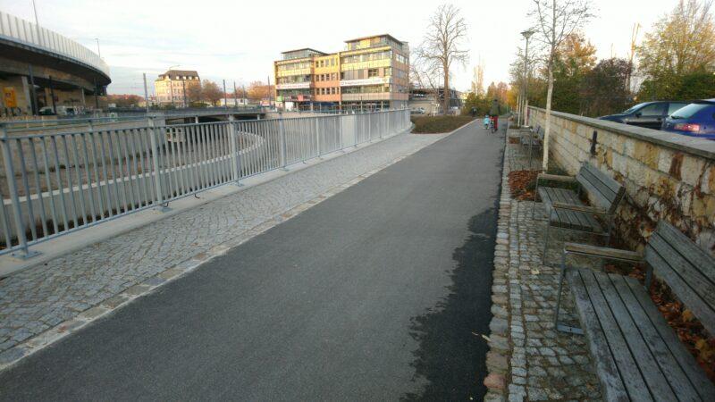 Radweg, links Gitter, rechts Bänke