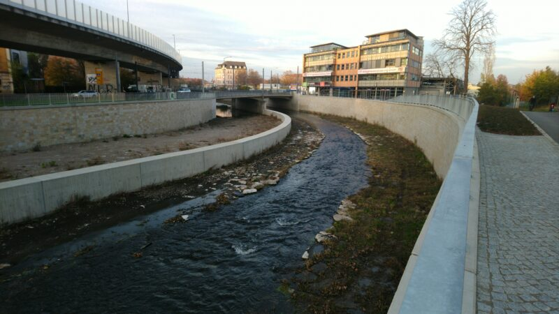 Fluß, links und rechts Hochwasserschutzmauern